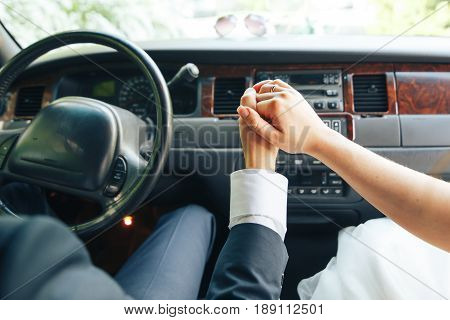 Closeup of the hands of the bride and groom in the wedding car