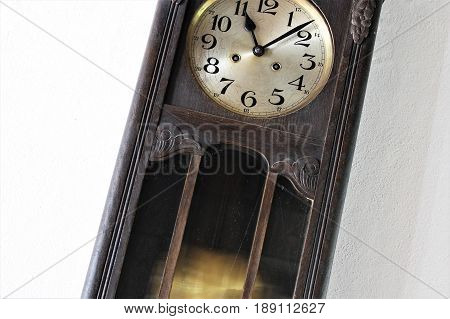 An Image of a vintage pendulum clock