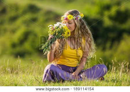 Beautiful woman smelling flowers at the meadow .
