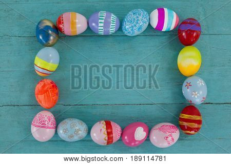 Various Easter eggs forming frame shape on wooden surface