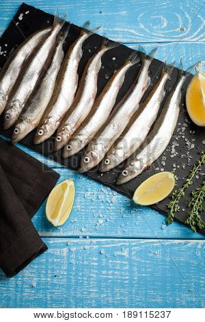 Fresh sea fish smelt or sardines ready for cooking with lemon, thyme, and coarse sea salt on a blue background. The concept of fresh, healthy seafood. Top view with copy space.