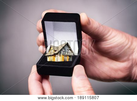 Hand holding black jewellery box with house