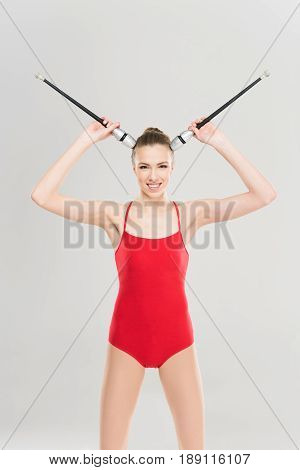 Young Smiling Caucasian Woman Rhythmic Gymnast Holding Clubs