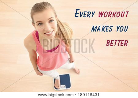Weight loss motivation concept. Young woman standing on scales at home. Text EVERY WORKOUT MAKES YOU BETTER on background