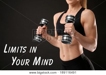 Sport motivation concept. Text LIMITS IN YOUR MIND and muscular woman with dumbbells on black background