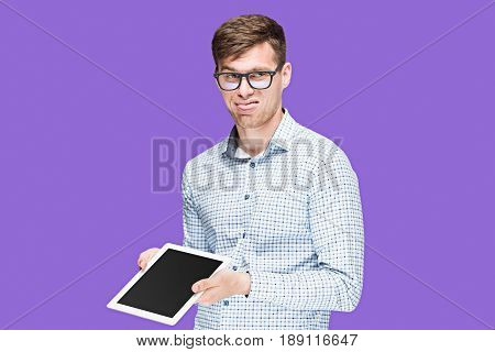 The young man in a shirt working on laptop on lilac studio background