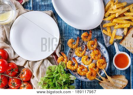 Variety of BBQ snack lunch. Plates grilled spicy king prawn kebabs, mushrooms skewers, bread, french fries potatoes, tomatoes, sauces and greens over blue wooden background. Flat lay, empty plates.