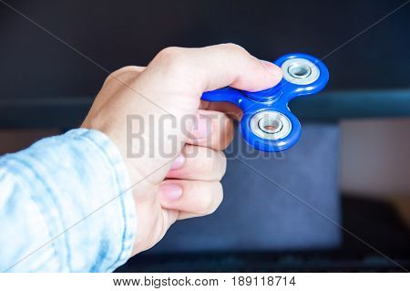 office Man's hand holds a spinner on the background of a personal computer close-up popular fidget spinner toy