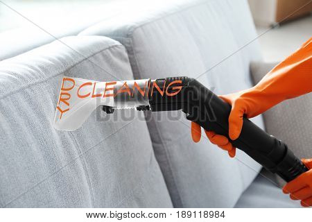 Concept of dry cleaning service. Employee removing dirt from furniture, closeup