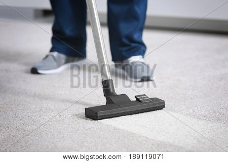 Cleaning service concept. Dry cleaner's employee hoovering carpet in flat, closeup