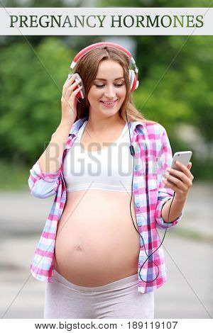 Pregnant young woman in headphones listening to music outdoor. Text PREGNANCY HORMONES