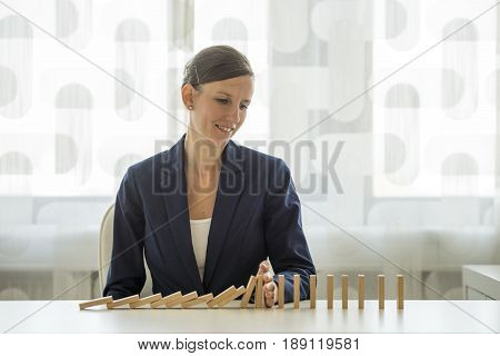 Businesswoman preventing dominoes from crumbling with palm on white wooden table.