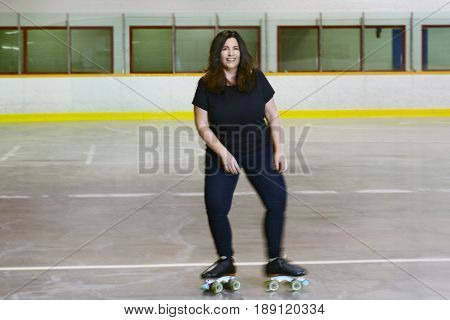 woman roller skating with motion blur in roller rink