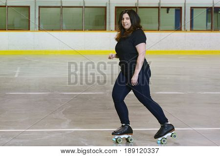 woman roller skating with quad skates in roller rink