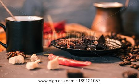 Black coffee cup and copper coffee pot and chocolate and sugar pieces and red chili peppers on black table with scattered coffee beans. Close up