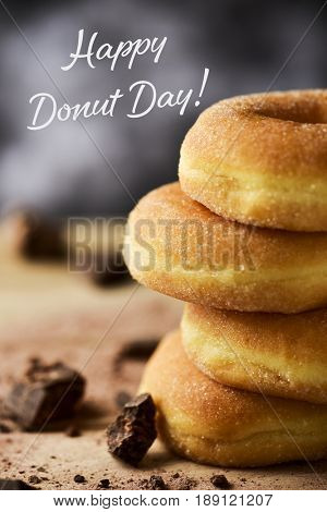 closeup of a pile of donuts glazed with a sugar icing on a rustic wooden table and the text happy donut day