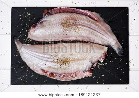 high-angle shot of a pair f raw filleted common sole on a slate tray placed on a rustic wooden table