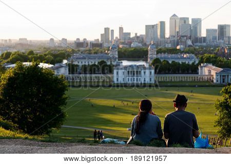 Couple having a picnic on the top of the hill at Greenwich Park, London during sunset