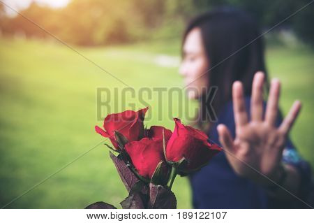 An Asian women reject a red rose flower from her boyfriend on Valentine's day with nature and blue sky background