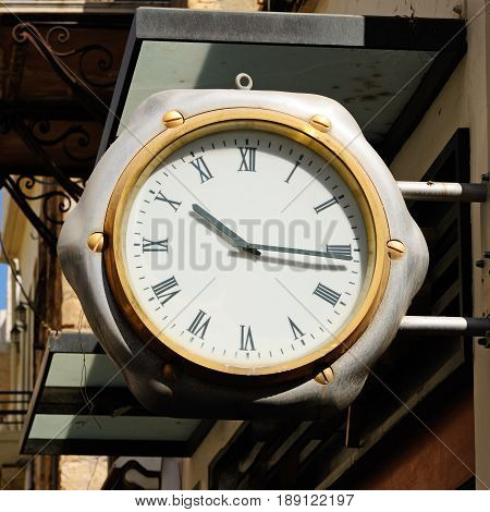 Street clock  on building wall close up