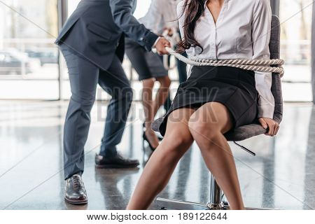 cropped view of businesswoman bound with rope on chair and businesspeople pulling her team spirit business concept