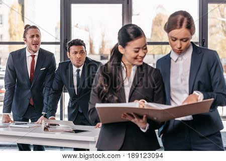 Young Businesswomen Working Together While Businessmen Grimacing Behind, Business Team Working Conce