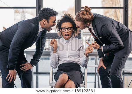 Two Emotional Businessmen In Formalwear Screaming On Businesswoman In Office, Multicultural Business