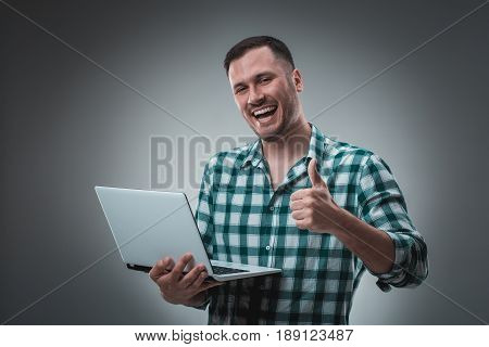 Portrait of young handsome man using laptop, wearing plaid shirt. Studio shot. Emotions