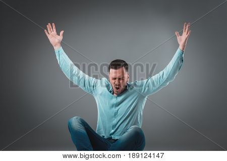 Casual young man sitting on the floor with his legs crossed and cheering with his hands in the air while screaming. Isolated on gray background