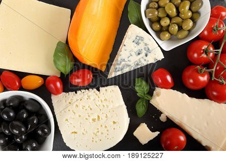 Food composition - different types of cheeses olives and tomatoes.