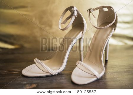 Beige open sandals with thin straps on high heels stand on a dark wooden floor against a background of a golden wall a front view.