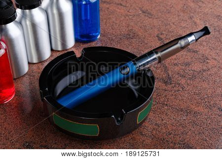 Electronic cigarette on the glass ashtray and bottles with vape liquid on granite surface.