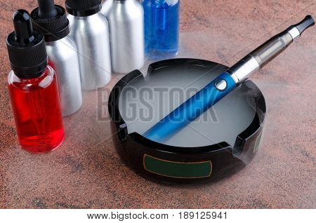 Electronic cigarette on glass ashtray and vape liquids within vapor on granite surface.
