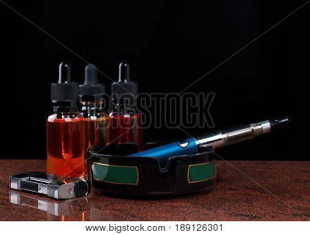 Electronic cigarette on ashtray, cigarette lighter and bottles with vape liquid on granite surface. Black background.