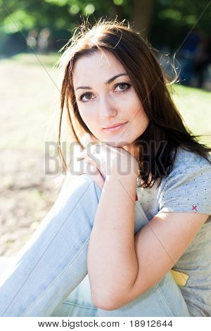 Beauty girl relaxes on the grass in the park near water