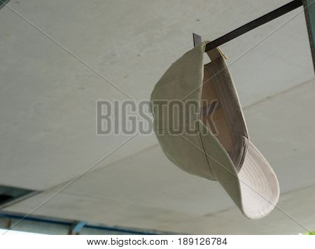 COLOR PHOTO OF CAP HANGING ON METAL BAR