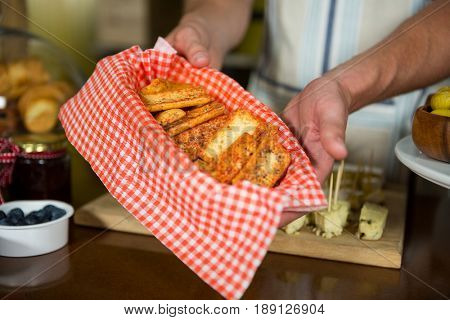 Staff holding tray of rusk at counter in grocery shop