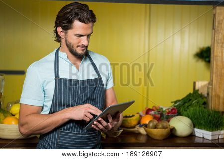 Shop assistant using digital tablet in health grocery shop