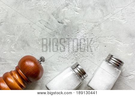 salt in glass bottle with saltcellar for spices set on gray table background top view mockup