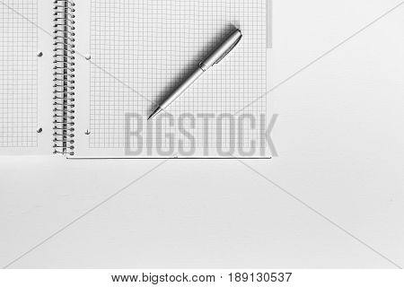Open Notebook In Cage With Pen On The Desktop