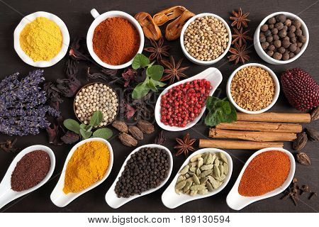 Colorful and aromatic herbs and spices on a dark wooden background.