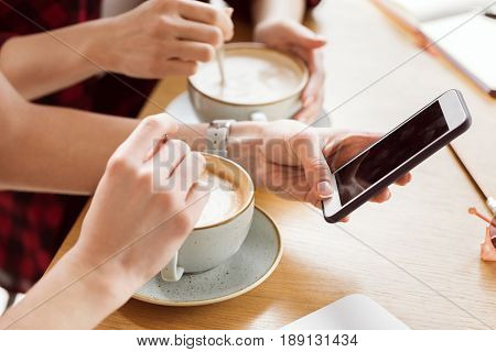 Close-up Partial View Of Young Women Sitting At Table And Drinking Coffee, Coffee Break Concept