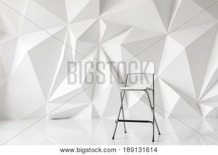 Modern chair on abstract background of polygons on white background. White texture.