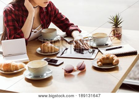 partial view of woman using digital tablet alone in cafe