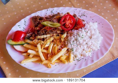 Traditional Hungarian goulash with rice, french fries and pepper close up.
