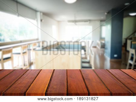 For your photomontage or product display Selected focus empty brown wooden table and Coffee shop or cafe blur background with bokeh image.