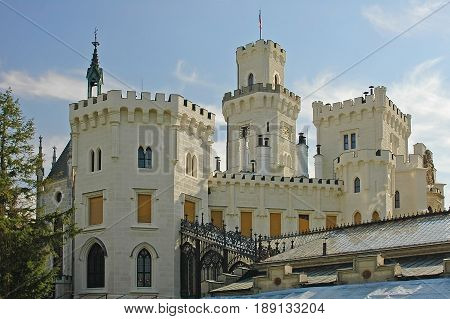 View on classic traditional white knight castle zamek Hluboka nad Vltavou, castle park garden. Classic knight walls and towers. Famous european Czech Republic castles sghtseeing tours