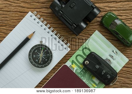 travel planning road trip concept with euro banknotes passport compass binoculars pencil paper note car key and miniature car on wood table.