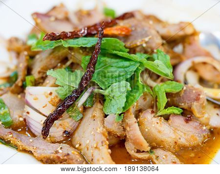 Slide grilled pork salad or Nam Tok garnish with mint leaves and dried chili. Nam Tok is spicy Northeast food of Thai flavors.