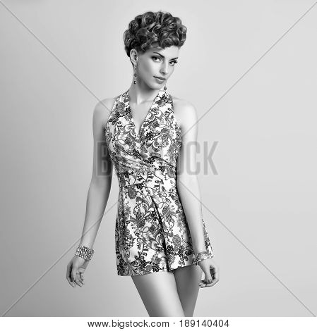 Fashion Model in Sexy Jumpsuit. Stylish Mohawk hairstyle. Beauty woman in Trendy Summer Dress, fashion Makeup, Summer Floral Outfit.Glamour fashion pose.Playful Girl, Luxury Accessories. Black and White